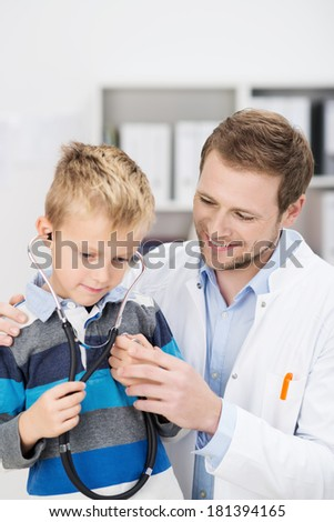 Cute young boy listening to his heartbeat with a stethoscope as the friendly male pediatrician puts him at his ease during a consultation at the hospital - stock photo