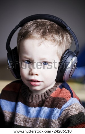 Cute young boy listening to music on headphones - stock photo