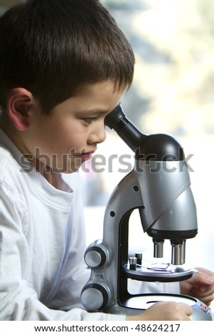 Cute young boy looks into his microscope