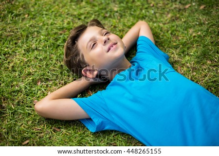 Cute young boy lying on grass in park