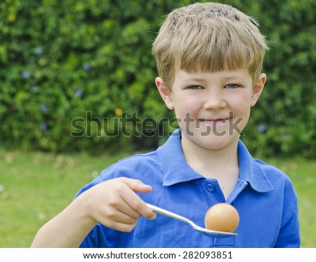 Cute young boy participating in the egg and spoon race at a traditional school sports day - stock photo