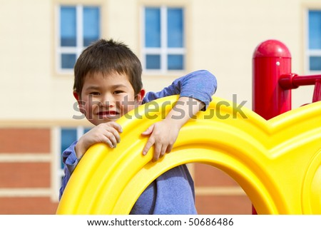 Cute young boy playing on playground equipment