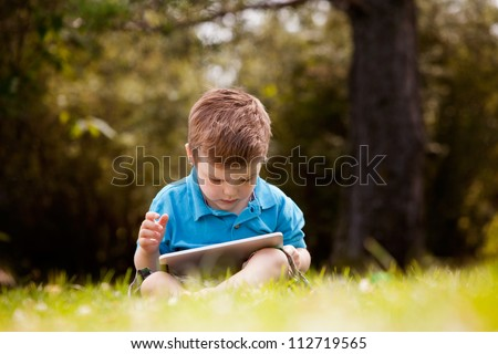 Cute young boy playing with a digital tablet outdoors in park - stock photo