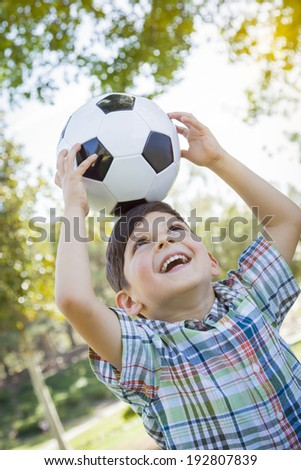 Cute Young Boy Playing with Soccer Ball Outdoors in the Park. - stock photo