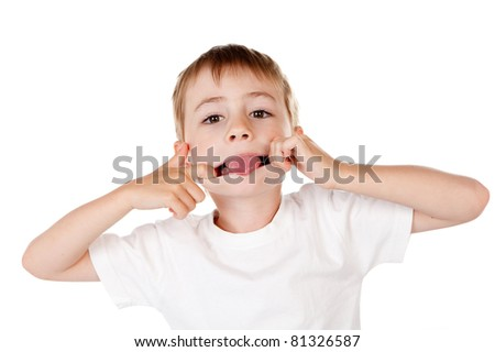 Cute young boy pulling funny face and sticking tongue out; white studio background.