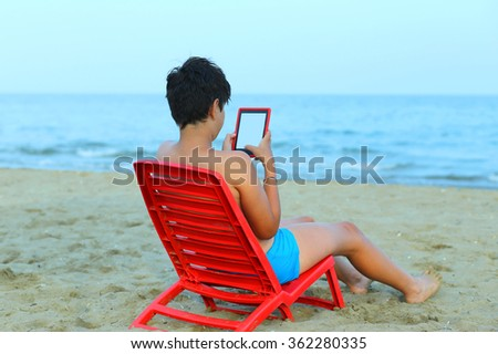 cute young boy reads an ebook on red chairs by the sea in summer