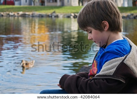 cute young boy sitting alone near a duck pond - stock photo