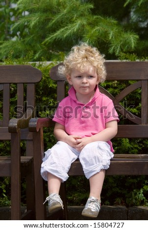 cute young boy sitting on a bench in summer - stock photo