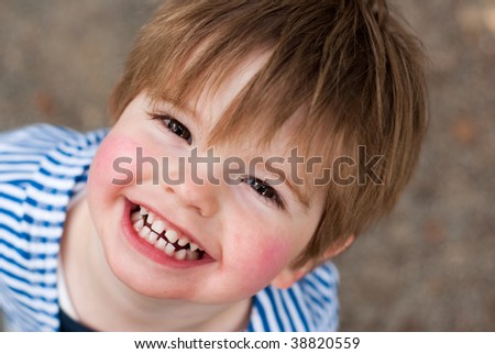 Cute young boy smiling up - stock photo