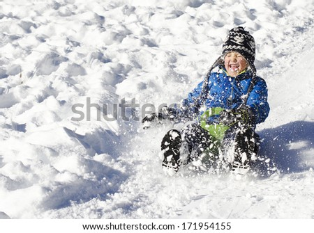 Cute young boy sprayed with snow as he is sledging - stock photo