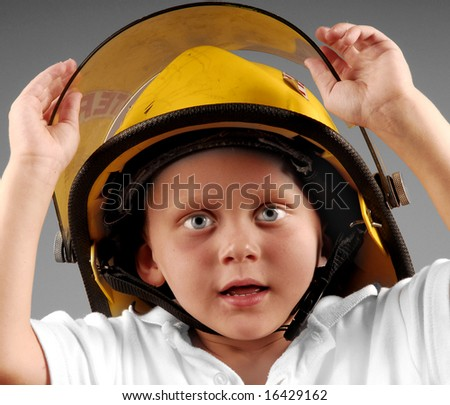 Cute young boy trying on fireman's rescue helmet - stock photo