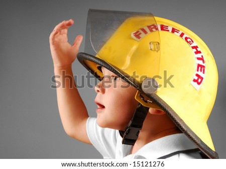 Cute young boy trying on real fireman's helmet - stock photo