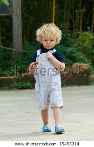 cute young boy walking in summer - stock photo