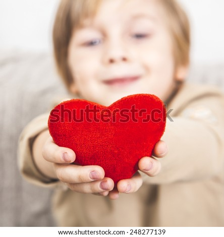 Cute young boy with a red heart in his hands