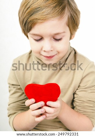 Cute young boy with a red heart in his hands - stock photo