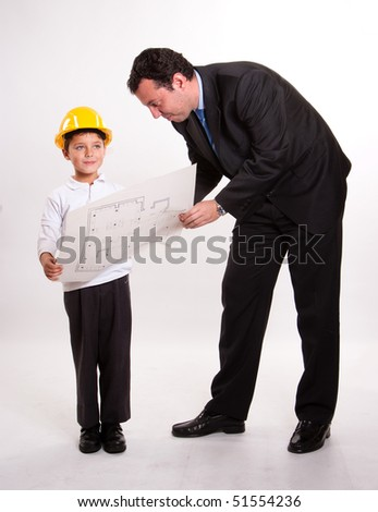 Cute young boy with a safety helmet holding a plan with his dad - stock photo