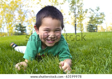 Cute young boy with great smile laying in the grass - stock photo