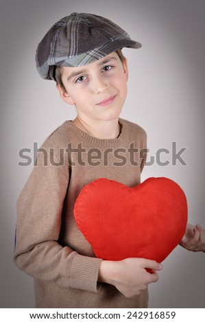 Cute young boy with newsboy cap holding a plush red heart on Valentines day - stock photo