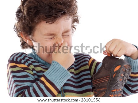 Cute young boy with stinky shoe pitching his nose - stock photo