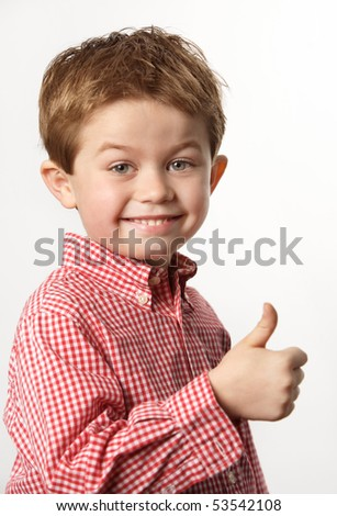 cute young boy with thumb up and smiling - stock photo