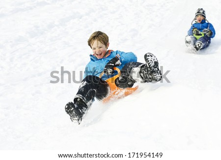 Cute young boys sledging in the snow - stock photo