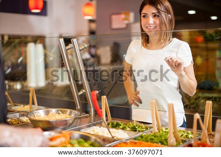 Cute young brunette choosing her favorite ingredients for a salad at a restaurant - stock photo
