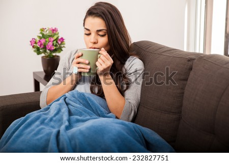 Cute young brunette covered in a blanket on a cold day enjoying a cup of tea - stock photo