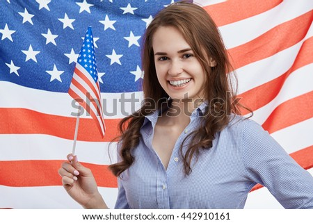 Cute young brunette girl celebrating National Independence Day on 4th of July in United States of America. Attractive model with cheerful toothy smile and flag on the background - stock photo