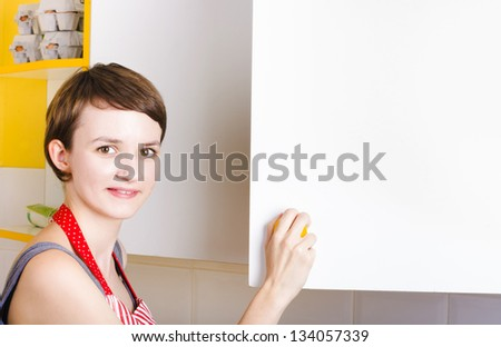 Cute young brunette woman with short hair looking for food ingredients in copyspace pantry cupboard in a food supplies conceptual - stock photo