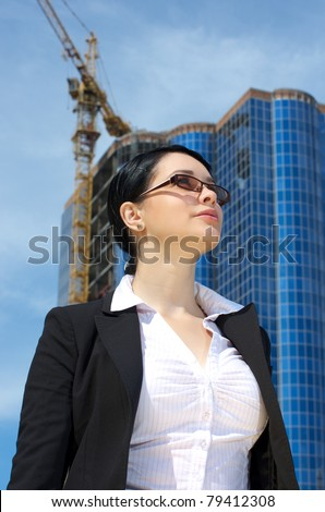 Cute young businesswoman. Skyscraper construction in distance. - stock photo