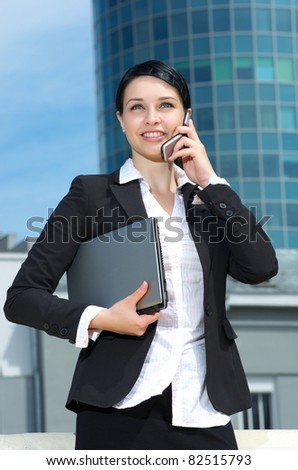 Cute young businesswoman talking cell phone - stock photo