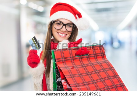 Cute young Caucasian brunette woman with Christmas hat shopping at the mall holding credit card and shopping bags. Santa Claus girl buying presents in shopping center. - stock photo