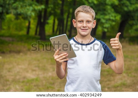 Cute young caucasian kid with freckles on his face in blue shorts and white and blue T-shirt and tablet and working in park and smiling. looking at camera, smiling with thumb up. - stock photo