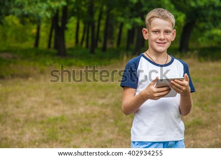 Cute young caucasian kid with freckles on his face in blue shorts and white and blue T-shirt and tablet and working in park and smiling. looking at camera and smiling. - stock photo