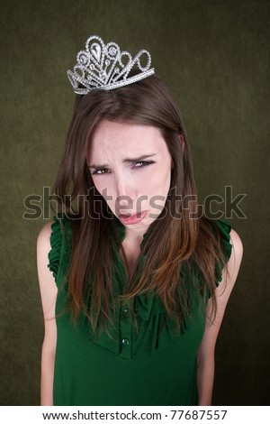 Cute young Caucasian woman with a crown tiara pouts - stock photo