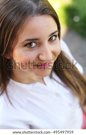 Cute young Caucasian  woman with long brown hair. Shot on a sunny summer day. She is wearing white shirt. Shot from above, high angle, top down.