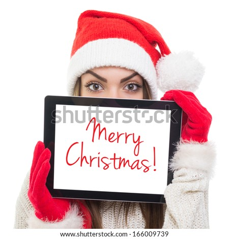 Cute young Caucasian woman with Santa hat hiding behind tablet computer with Merry Christmas text on screen. Isolated on white background. - stock photo