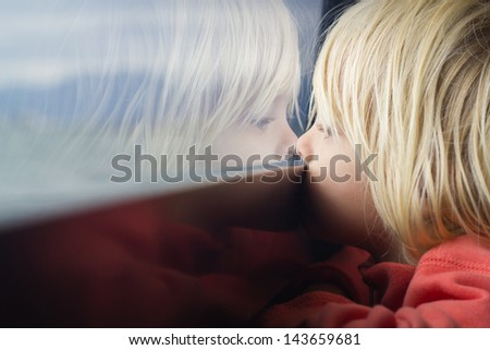 Cute young child deep in thought looking out of a window - stock photo