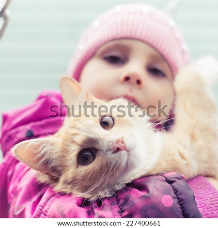 Cute young child holding kitten. - stock photo