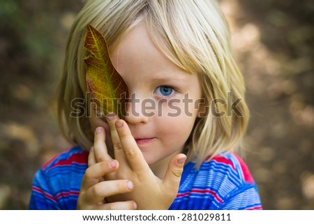 Cute young child in nature holding a leaf over eye - stock photo