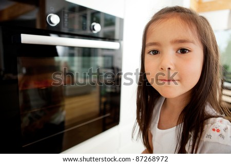 Cute young child looking at camera while cookies bake in oven - stock photo