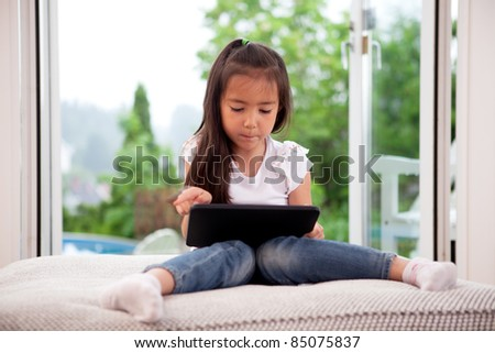 Cute young child using a digital tablet in a home interior with large window - stock photo
