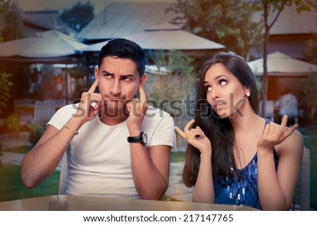 Cute Young Couple Arguing - Young adult couple arguing with funny expressions and gestures, out on a date