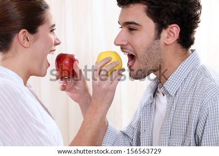 cute young couple eating apples - stock photo