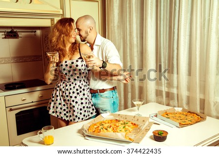 Cute young couple flirting at a party with alcohol and pizza. Celebrate, disco, party, nightlife, entertainment, friendship concept. - stock photo