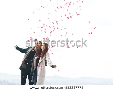 Cute young couple in love, outdoors with hearts falling