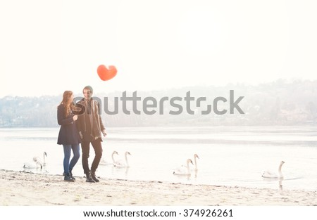 Cute young couple in love, walking at the riverside, with a red balloon and swans  - stock photo