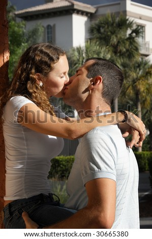 cute young couple kissing outside in tropical setting - stock photo