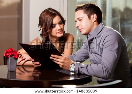 Cute young couple looking at a menu and deciding what to order at a coffee shop