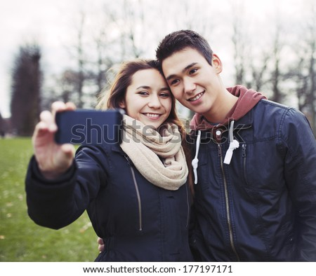 Cute young couple looking happy while taking pictures using a smart phone at the park. Mixed race teenage boy and girl in love photographing themselves outdoors. - stock photo